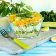 Delicious salad with eggs, cabbage and cucumbers on blue wooden table — Стоковая фотография