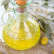 Olive oil and branch on sackcloth close up — Stock Photo