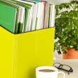 Magazines and folders in green box,on office interior background — Stok fotoğraf