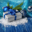 Composition with Christmas balls, gift box and snow on color wooden background — ストック写真