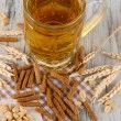 Beer in glass crunches, and nuts on napkin on wooden table — 图库照片
