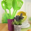 Plastic kitchen utensils in stand with clean dishes on table on bright background — Stock Photo
