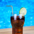 Tasty cocktail on swimming pool background — Stock Photo