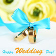 Wedding rings tied with ribbon on white fabric background — Stock Photo