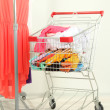 Shopping cart with clothing, on gray wall background — Stock Photo #34499731