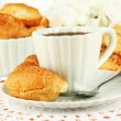 Tasty croissants and cup of coffee on table close-up — Stock Photo #34499739