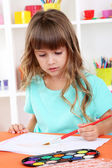 Little girl draws sitting at table in room on shelves background — Photo