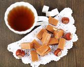 许多太妃糖和杯茶在木制的桌子上的餐巾纸上 — 图库照片