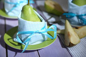 Pears in napkins on plates on wooden table close-up — Stock Photo