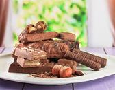 πλάκα με νόστιμα σοκολάτα μπαρ στο τραπέζι σε φωτεινό φόντο — 图库照片
