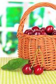 Cherry berries in wicker basket on table in room — Stock Photo