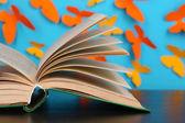Открыл книгу на деревянный стол на фоне бабочек — Стоковое фото