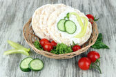 Tasty crispbreads with vegetables on wooden background — Stock Photo