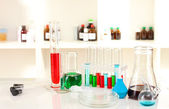 Cristalería de laboratorio diferentes con líquido de color sobre fondo de laboratorio — Foto de Stock