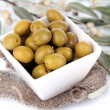 Olives in bowl with branch on sackcloth close up — Stock Photo