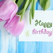 Stock Photo: Beautiful bouquet of purple tulips and blank card on blue wooden background