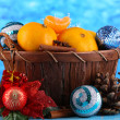 Christmas tangerines in basket on blue background — Photo