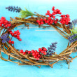Wreath of dry branches with flowers on wooden table close-up — Stock fotografie
