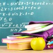 Purple backpack with school supplies on wooden table on green desk background — Stock Photo #34503561