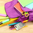 Purple backpack with school supplies on wooden background — Stock Photo #34503633