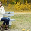 Stock Photo: Young lonely woman on bench in park