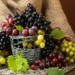 Assortment of ripe sweet grapes in basket, on brown background — Stock Photo