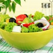 Greek salad on plate on table on light background — Stock Photo