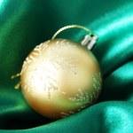 Beautiful Christmas ball on green satin cloth — Stock Photo