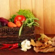 Different vegetables in basket with yellow leaves on table on wooden background — Stock Photo