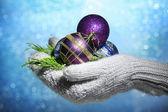Kadın eldivenler Noel ağacı toplar, renkli arka plan üzerinde eller — Stok fotoğraf