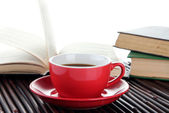 Cup of coffee and books on bamboo mat on white background — Stock Photo