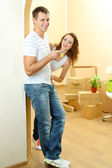 Young couple with keys to your new home on room background — Stock Photo