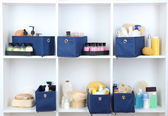 Blue textile boxes with cosmetic products for personal care in white shelves — Stock Photo