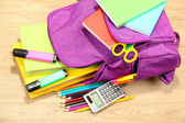 Lila ryggsäck med skolan levererar på trä bakgrund — Stockfoto