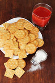 Delicious crackers with salt and tomato juice on wooden background — Foto Stock