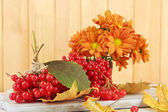 Red berries of viburnum and vase with flowers on table on wooden background — Stock Photo