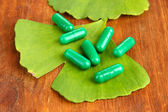 Ginkgo biloba leaves and pills on wooden background — Stock Photo
