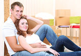 Young couple with boxes in new home on room background — Stock Photo