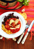 Chili Corn Carne - traditional mexican food, on white plate, on napkin, on wooden background — Stock Photo