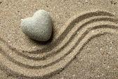 Grey zen stone in shape of heart, on sand background — Stock Photo