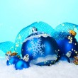 Beautiful blue Christmas balls and cones in snow on blue background — Stock Photo