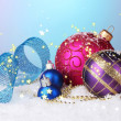 Beautiful Christmas balls and cones on snow on bright background — Stock Photo #34635859
