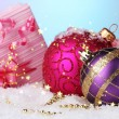 Beautiful Christmas balls and gifts on snow on bright background — Stock Photo