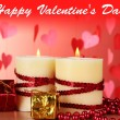 Beautiful candles with romantic decor on a wooden table on a red background — Stok fotoğraf