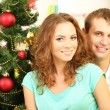Happy young couple near Christmas tree at home — Stock Photo #34636329