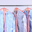 Office male clothes in cases for storing on hangers, on gray background — Photo