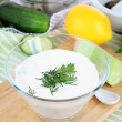 Cucumber yogurt in glass bowl, on color napkin, on wooden background — Stock fotografie