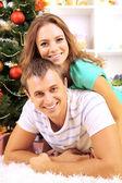 Gelukkige jonge paar in de buurt van kerstboom thuis — Stockfoto