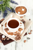 Cocoa powder in cup on napkin on wooden table — Stock Photo