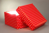 Gift box with bright light on it on grey background — Foto de Stock